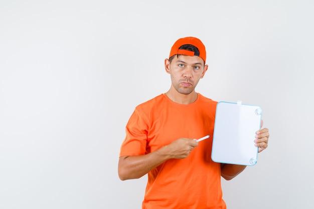 Levering man in oranje t-shirt en pet die pen op wit bord richt en er serieus uitziet