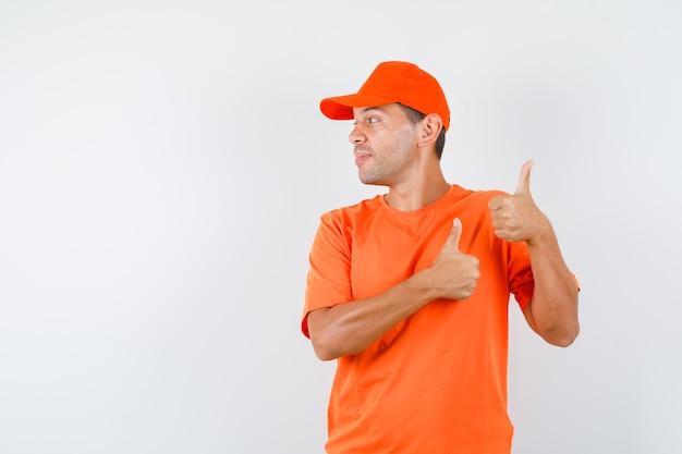 Levering man in oranje t-shirt en pet duimen opdagen terwijl opzij kijken en vrolijk kijken
