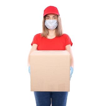 Levering man in rode dop leeg t-shirt uniform steriel gezichtsmasker handschoenen geïsoleerd op gele achtergrond studio guy werknemer werken koerier service quarantaine pandemisch coronavirus virus concept