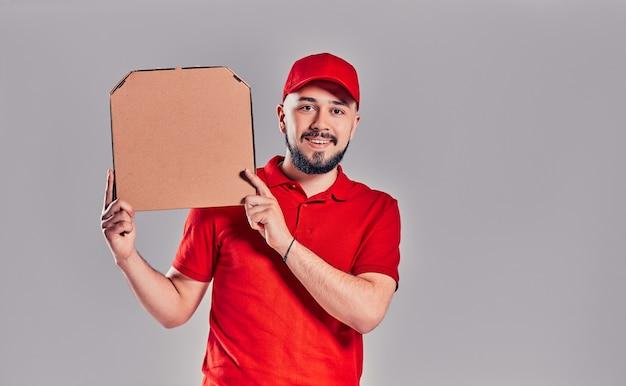 Levering man in rode dop, t-shirt geven eten bestellen pizzadozen geïsoleerd op een grijze achtergrond. mannelijke werknemer pizzaman koerier met pizza in lege lege kartonnen flatbox kopieerruimte. serviceconcept