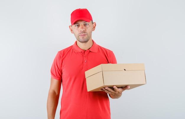Levering man in rode pet en t-shirt met kartonnen doos en op zoek zelfverzekerd