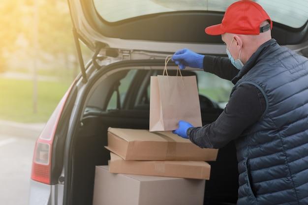 Levering man in rode pet, medische gezichtsmasker en handschoenen houden papieren zak in de buurt van de auto buiten