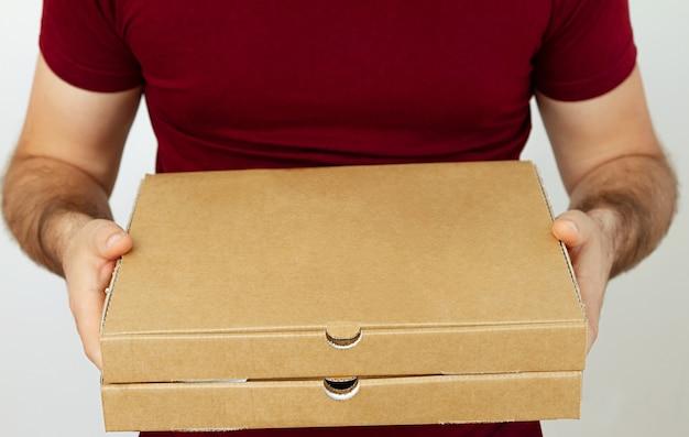 Levering man in rode t-korte kartonnen dozen pizza op witte achtergrond te houden. pizza bezorging. koerier naar huis.