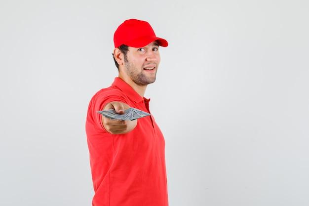 Levering man in rood t-shirt, pet dollarbiljetten uitrekken en er positief uitzien.