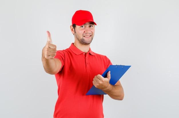Levering man in rood t-shirt, pet klembord met duim omhoog houden en er vrolijk uitzien