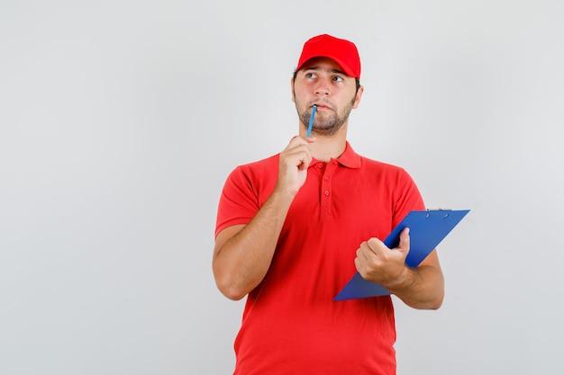 Levering man in rood t-shirt, pet opzoeken met klembord en potlood en peinzend kijken