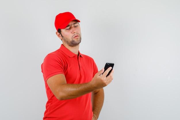 Levering man in rood t-shirt, pet smartphone kijken en peinzend kijken