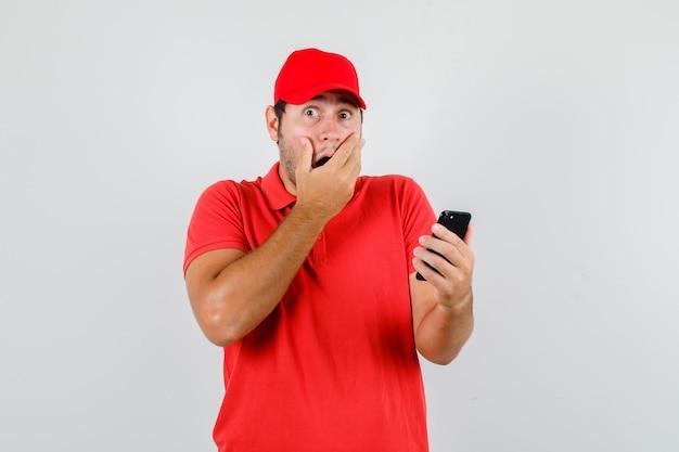 Levering man in rood t-shirt, pet smartphone met hand op mond houden en verbaasd kijken