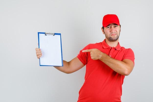 Levering man in rood t-shirt, pet wijzend op klembord en kijkt verveeld