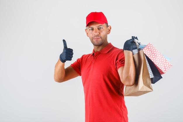 Levering man in rood uniform, handschoenen met papieren zakken en duim opdagen en tevreden kijken