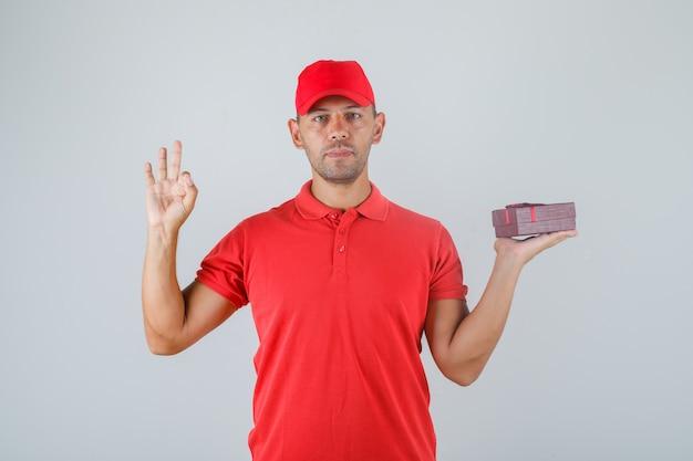 Levering man in rood uniform huidige doos houden en ok teken tonen