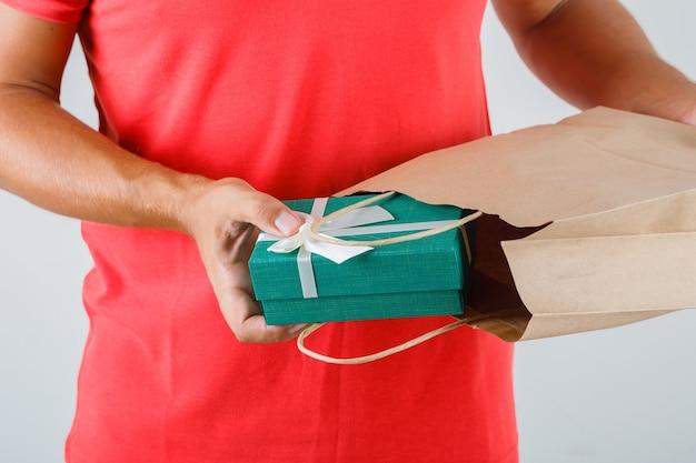 Levering man in rood uniform huidige doos uit papieren zak nemen