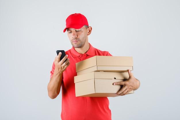 Levering man in rood uniform kartonnen dozen te houden tijdens het gebruik van smartphone