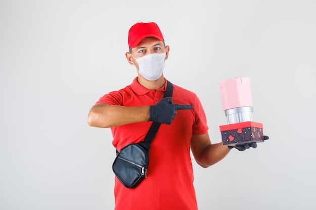 Levering man in rood uniform, medisch masker, handschoenen wijzende vinger op geschenkdozen