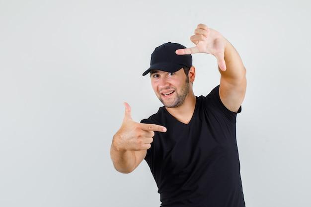 Levering man in zwart t-shirt, pet frame gebaar maken en op zoek vrolijk