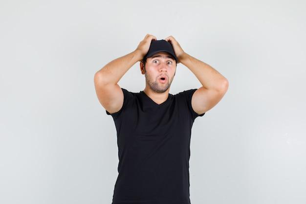 Levering man in zwart t-shirt, pet hand in hand op het hoofd en op zoek geschokt