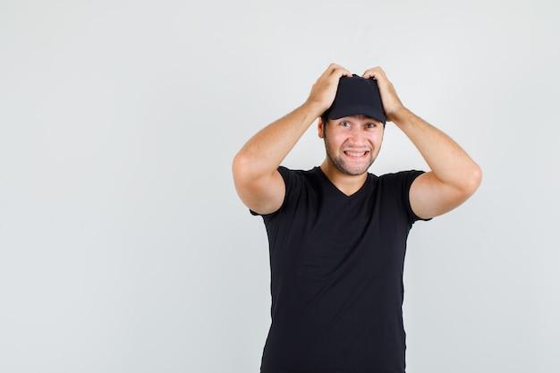 Levering man in zwart t-shirt, pet hand in hand op het hoofd en op zoek vrolijk