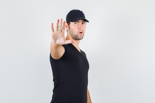 Levering man in zwart t-shirt, pet toont geen gebaar en kijkt serieus