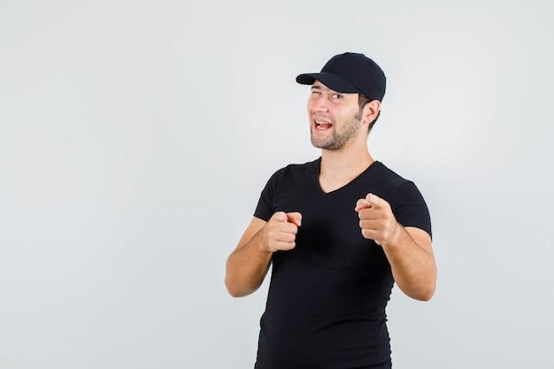 Levering man in zwart t-shirt, pet wijzend op camera met knipperende ogen en op zoek blij