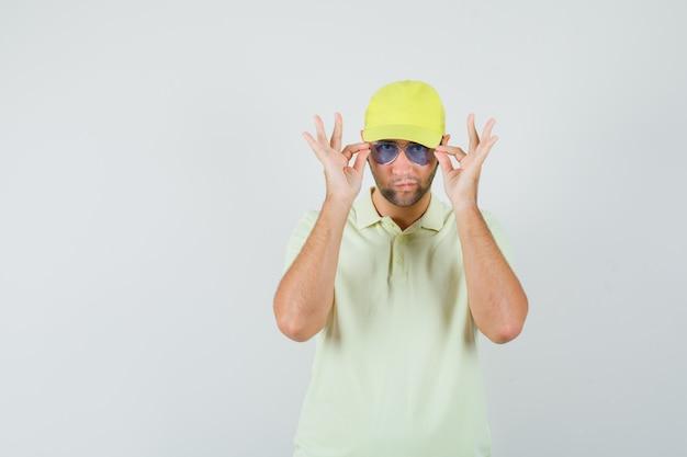 Levering man kijkt door een bril in geel uniform en kijkt aarzelend, vooraanzicht.