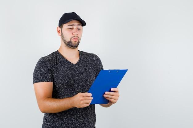 Levering man kijkt uit over notities op klembord in t-shirt en pet en kijkt voorzichtig