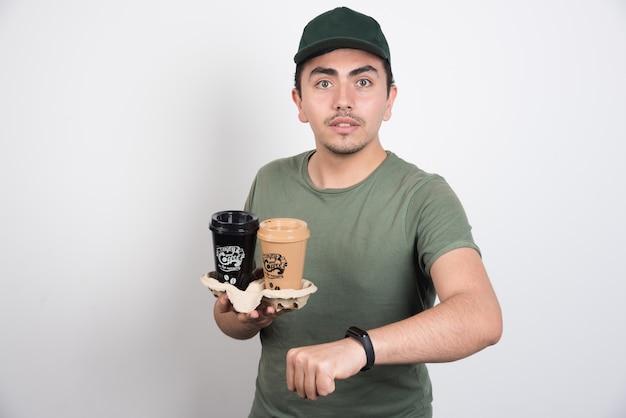 Levering man met afhaalmaaltijden kopjes koffie op witte achtergrond.