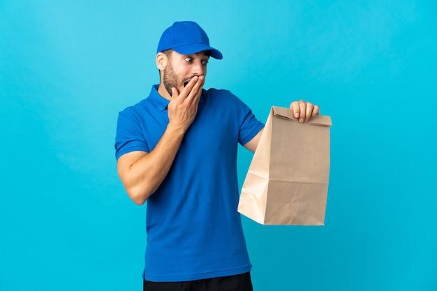Levering man met baard geïsoleerd op blauwe muur met verrassing en geschokte gelaatsuitdrukking