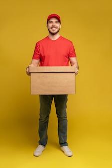 Levering man met doos in studio geïsoleerd op gele muur
