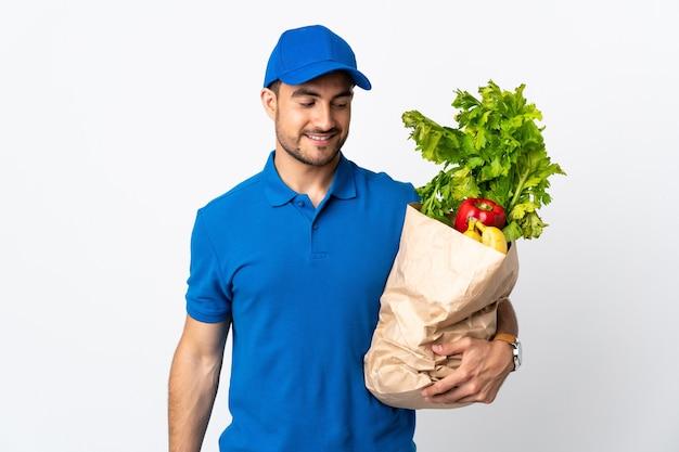 Levering man met groenten geïsoleerd op een witte muur met gelukkige uitdrukking