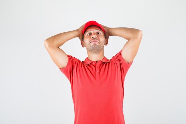 Levering man met hoofd in handen in rood uniform en op zoek verward. vooraanzicht.
