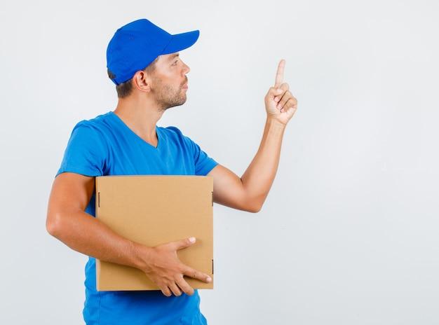 Levering man met kartonnen doos met vinger omhoog in blauw t-shirt