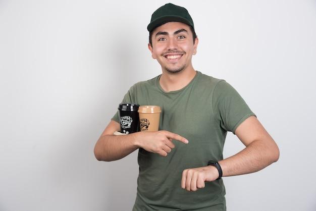 Levering man met kopjes koffie en zijn horloge te wijzen.
