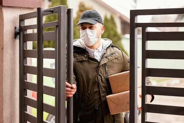 Levering man met pakket masker dragen