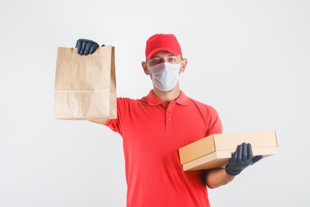 Levering man met papieren zak en kartonnen doos in rood uniform, medisch masker, handschoenen vooraanzicht.