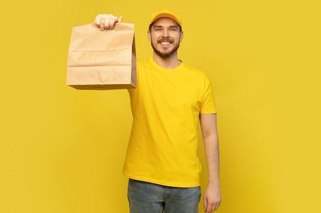 Levering man met papieren zak met voedsel op gele achtergrond.