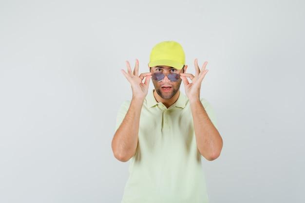 Levering man opstijgen bril in geel uniform en verdacht, vooraanzicht op zoek.