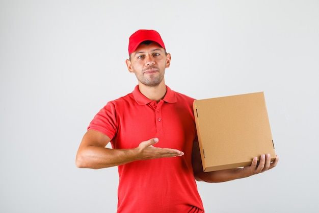 Levering man pizzadoos tonen in zijn hand in rood uniform