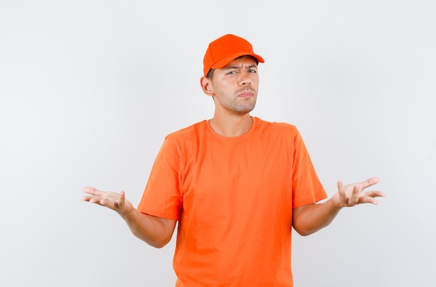 Levering man verhogen handen op vragende manier in oranje t-shirt en pet en op zoek verward