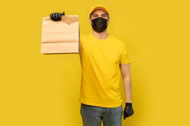 Levering man werknemer in gele pet t-shirt uniform masker handschoen houden ambachtelijke papieren pakket met voedsel geïsoleerd