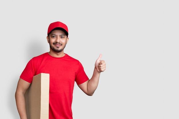 Levering man werknemer in rode dop leeg t-shirt thumbsup uniform houden lege kartonnen doos geïsoleerd op een witte achtergrond