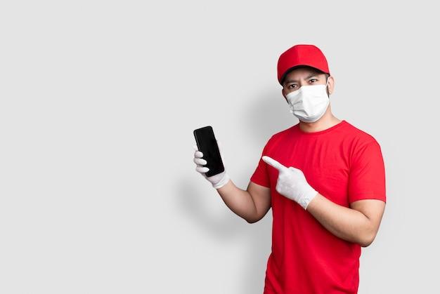 Levering man werknemer in rode dop leeg t-shirt uniform gezichtsmasker houden zwarte mobiele telefoontoepassing geïsoleerd op wit
