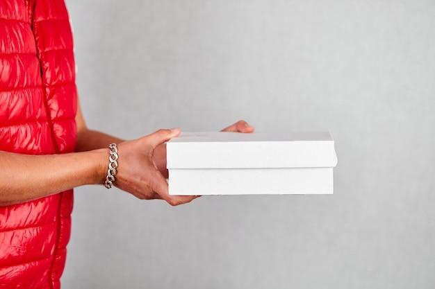 Levering man werknemer in rood vest uniform houden lege kartonnen doos geïsoleerd op grijze muur, service quarantaine pandemie coronavirus, contactloze levering.
