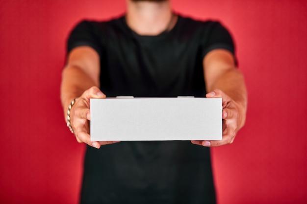 Levering man werknemer in zwart uniform houden lege kartonnen doos geïsoleerd