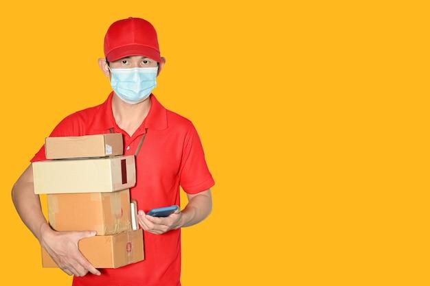 Levering man werknemer pet en shirt rood uniform gezichtsmasker houder pakket