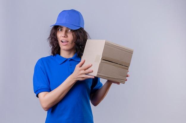 Levering meisje in blauw uniform en glb bedrijf doos pakket op zoek verrast staande op geïsoleerde wit