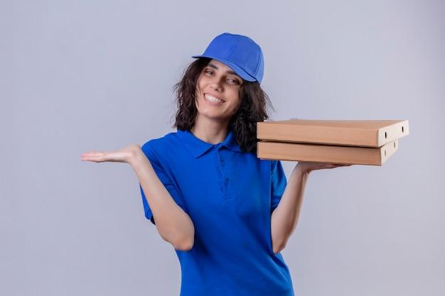 Levering meisje in blauw uniform en pet houden van pizzadozen presenteren met arm van de hand glimlachend vrolijk staan