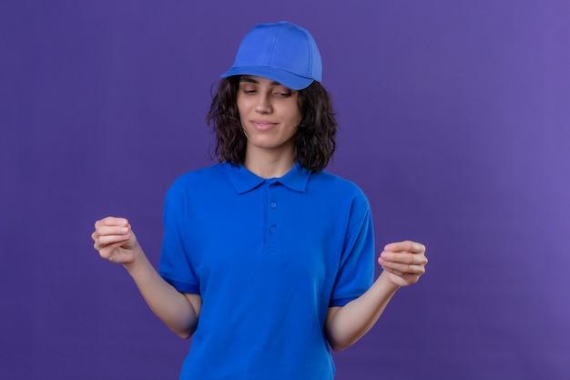 Levering meisje in blauw uniform en pet op zoek zelfverzekerd gebaren met de hand, lichaamstaal concept staande op geïsoleerde paars