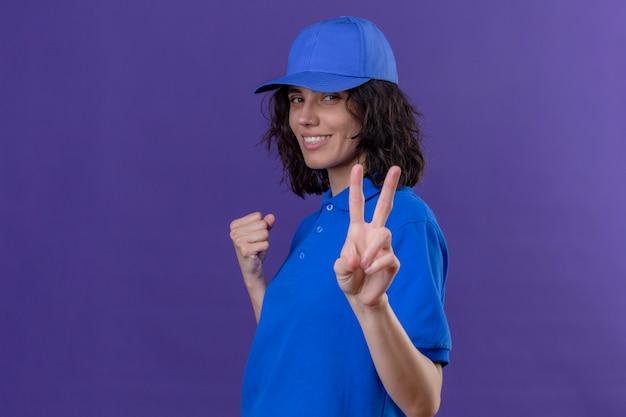 Levering meisje in blauw uniform en pet verhogen vuist met overwinningsteken glimlachend zelfverzekerd staande op geïsoleerde paars