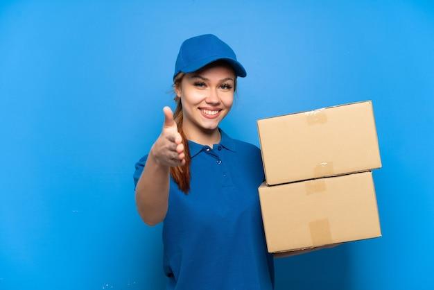 Levering meisje over geïsoleerde blauwe muur handen schudden voor het sluiten van een goede deal