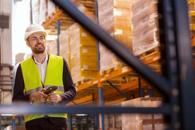 Levering op grote schaal. positieve aardige man kijken naar de dozen tijdens het werken in een leveringsmagazijn